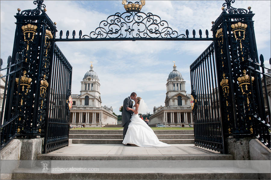 A newlywed bride and groom kiss at Greenwich's Old Royal Naval College (ORNC) after their summer Trafalgar Tavern wedding . Photo by Greenwich photographer Rebecca Portsmouth