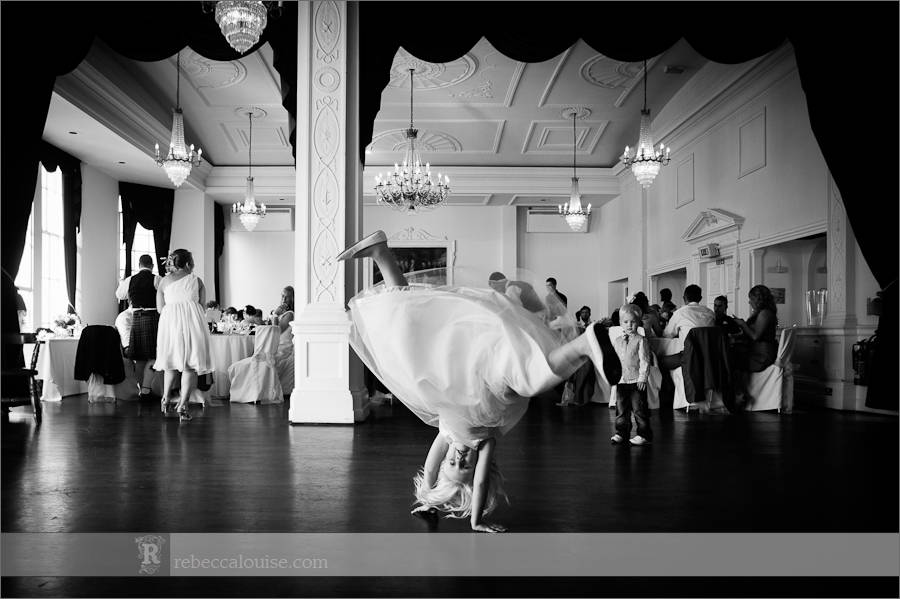 A bridesmaid does cartwheels across the Trafalgar Tavern's banqueting suite at a summer wedding.