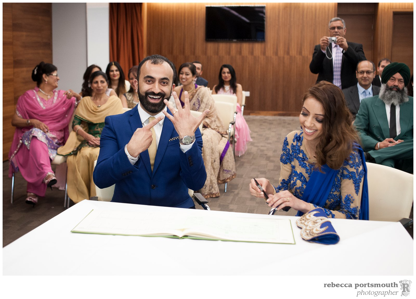While the groom shows of his brand new wedding ring, his bride gets ready to sign the register during their Chelsea Football Club wedding. Photographer: Rebecca Portsmouth
