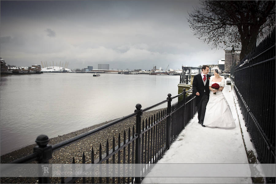 Bride and groom Louise + Charlie walking along the Thames near the Trafalgar Tavern with the O2 of North Greenwich in the background, during their wedding portraits.