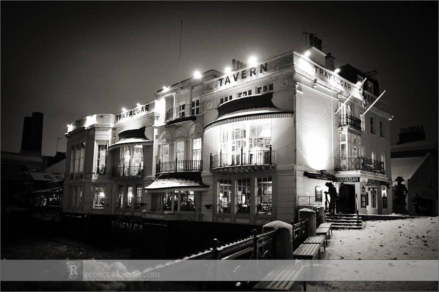 The Trafalgar Tavern wedding venue in Greenwich lit up at night in winter, with snow on the ground.