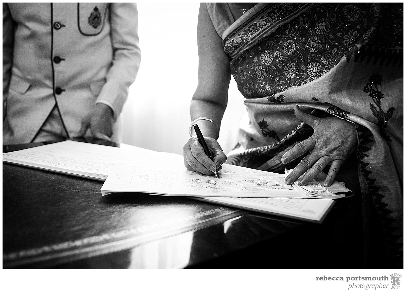 The groom's mother signs the wedding registry at Chelsea Old Town Hall's Brydon Room after the civiil marriage of Pooja and Ankit.
