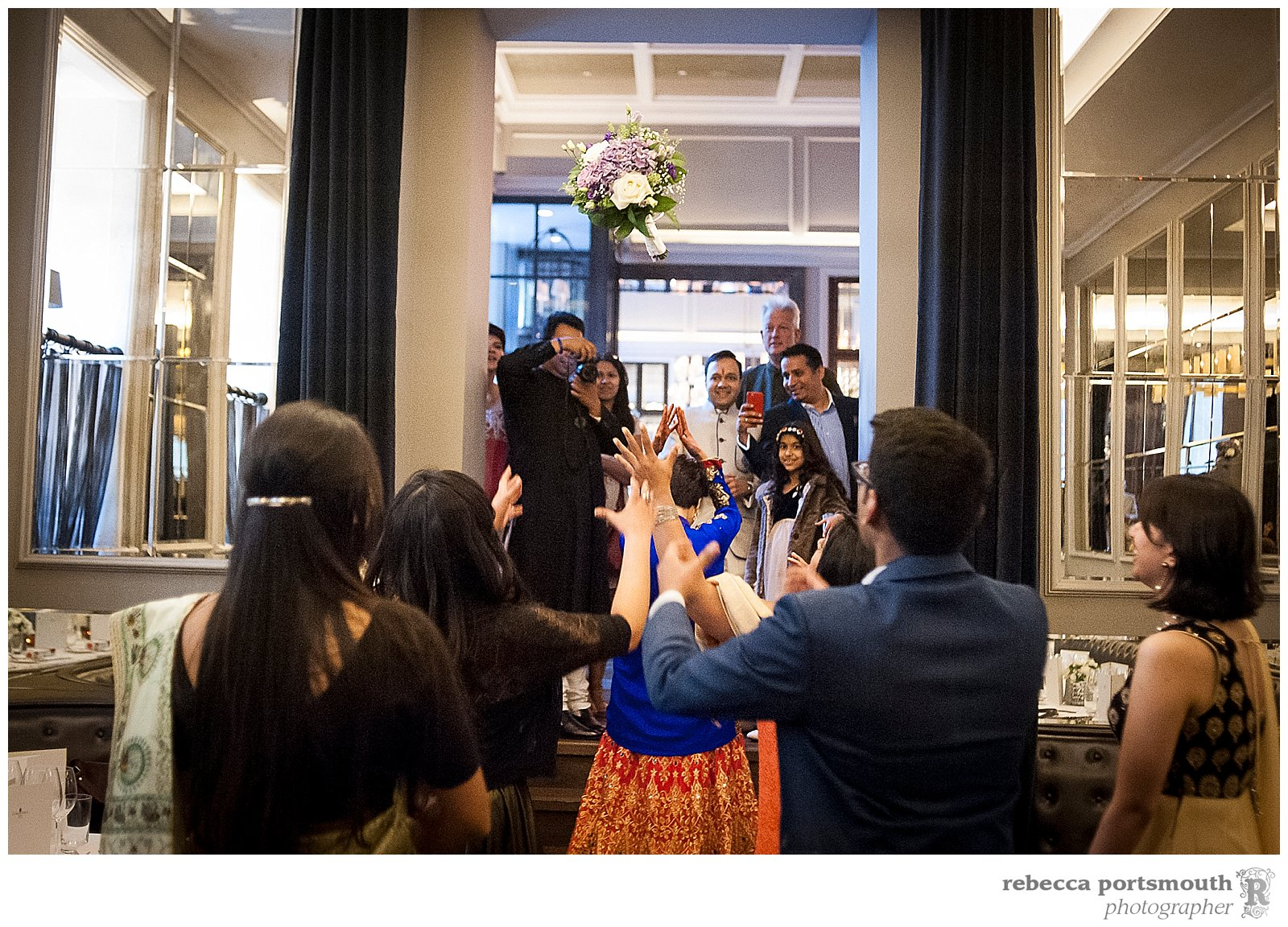 Pooja throws her bouquet at her wedding reception at the Corinthia Hotel, Whitehall Place, London.