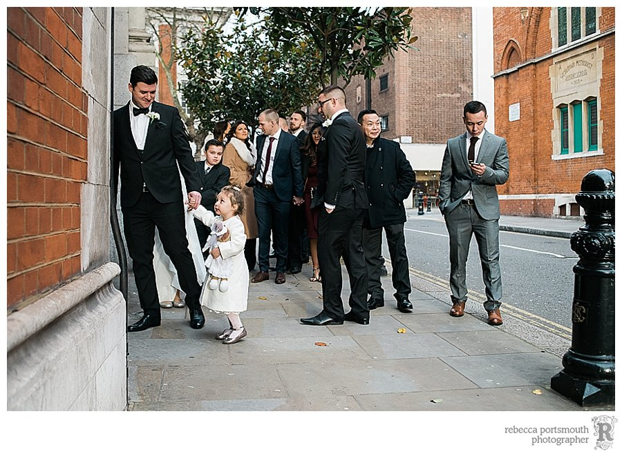 The groom and his daughter arrive at the side entrance of Chelsea Old Town Hall on Kings Road, ready for their civil wedding ceremony.
