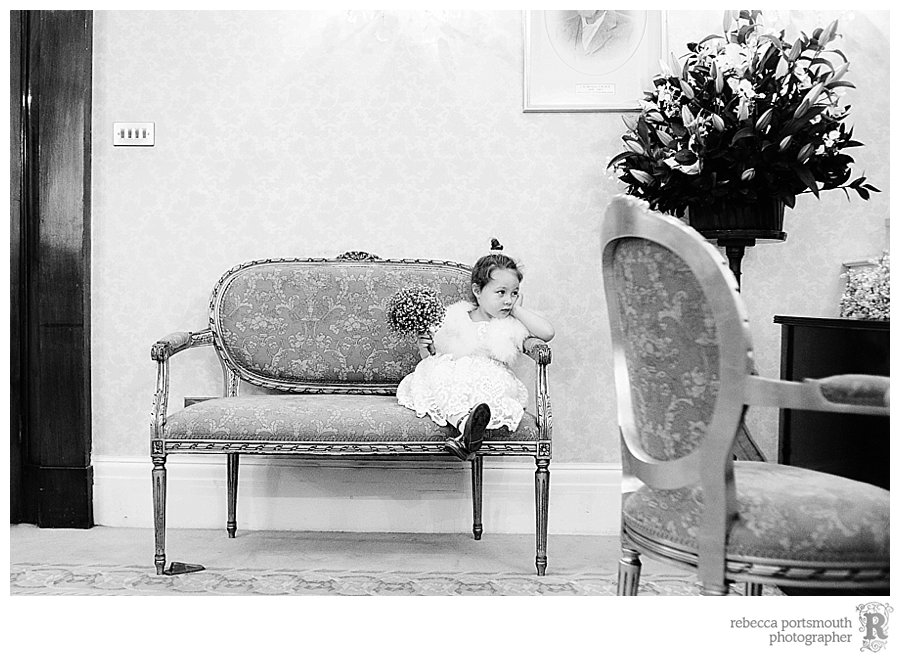 The bride and groom's daughter + flowergirl waits for all the paperwork to be done.