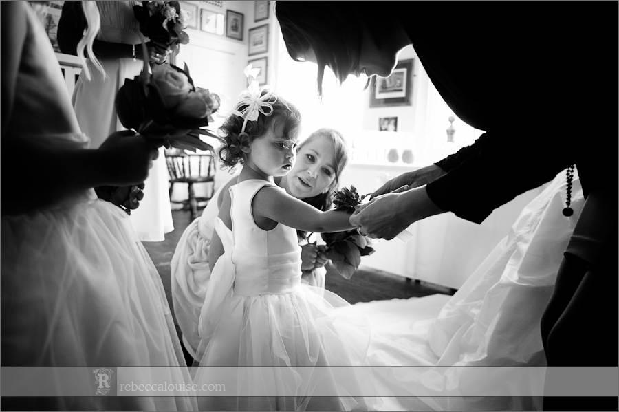 A flowergirl has her corsage put on before Jane and Ian's summer Trafalgar Tavern wedding