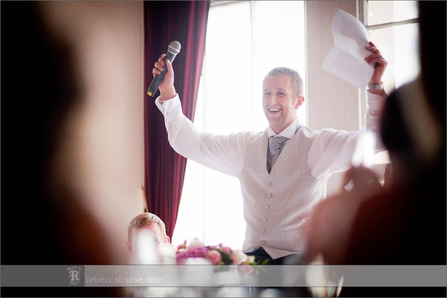 The groom cheers during his speech at his Trafalgar Tavern wedding reception.