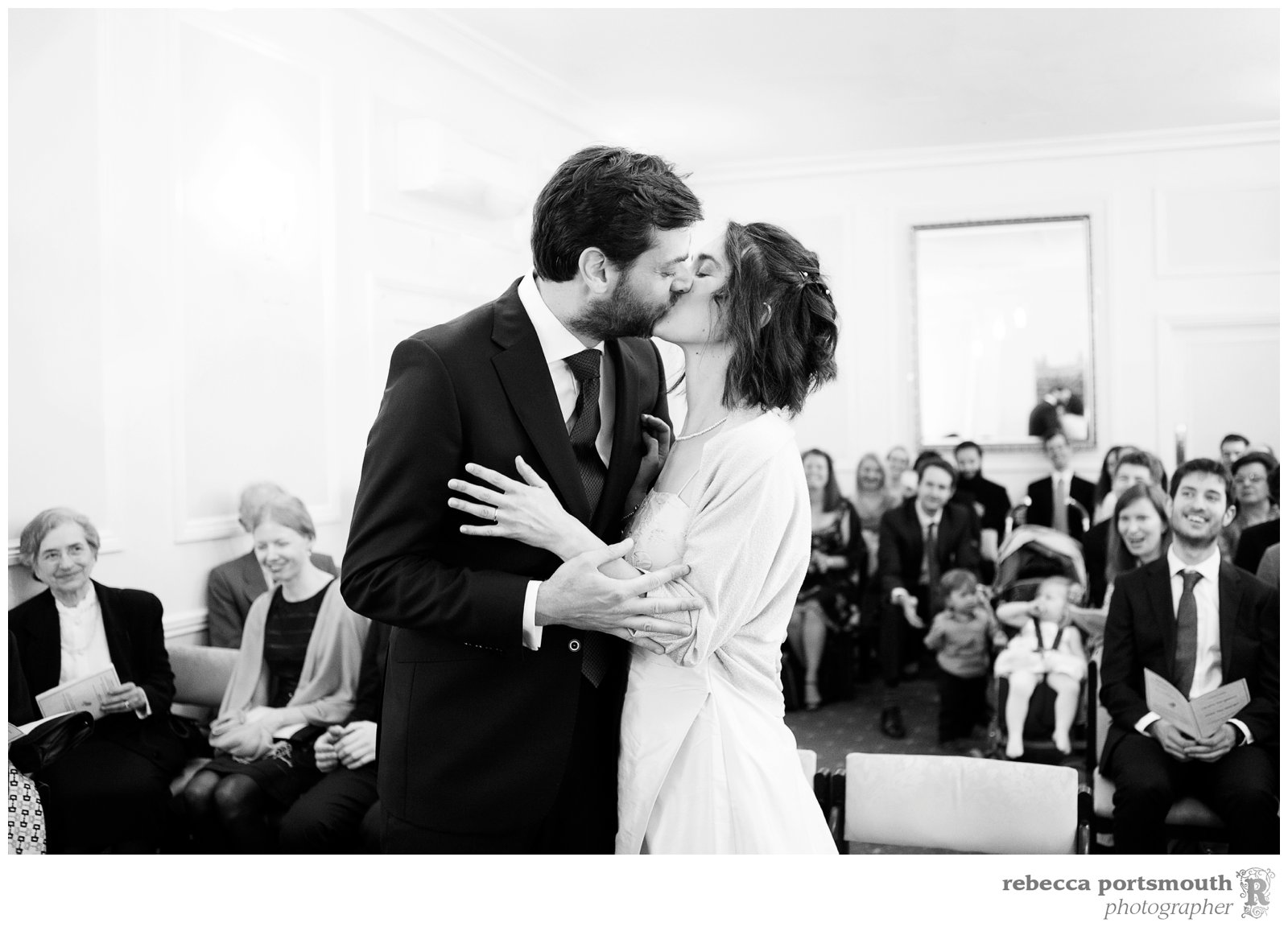 Cambridge Register office wedding - the bride and groom kiss in front of their guests.