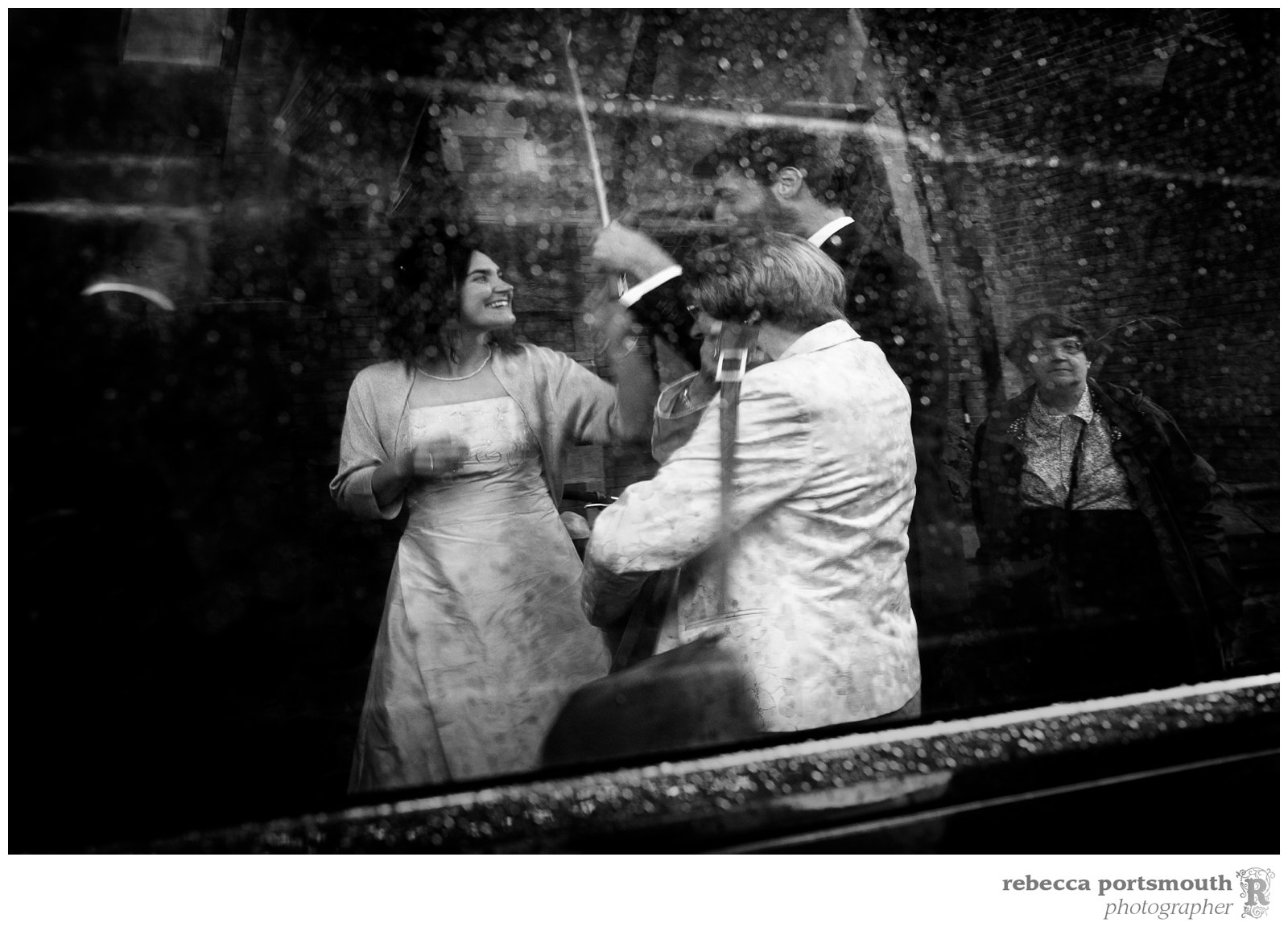 The bride and groom are reflected in a rainy van window.