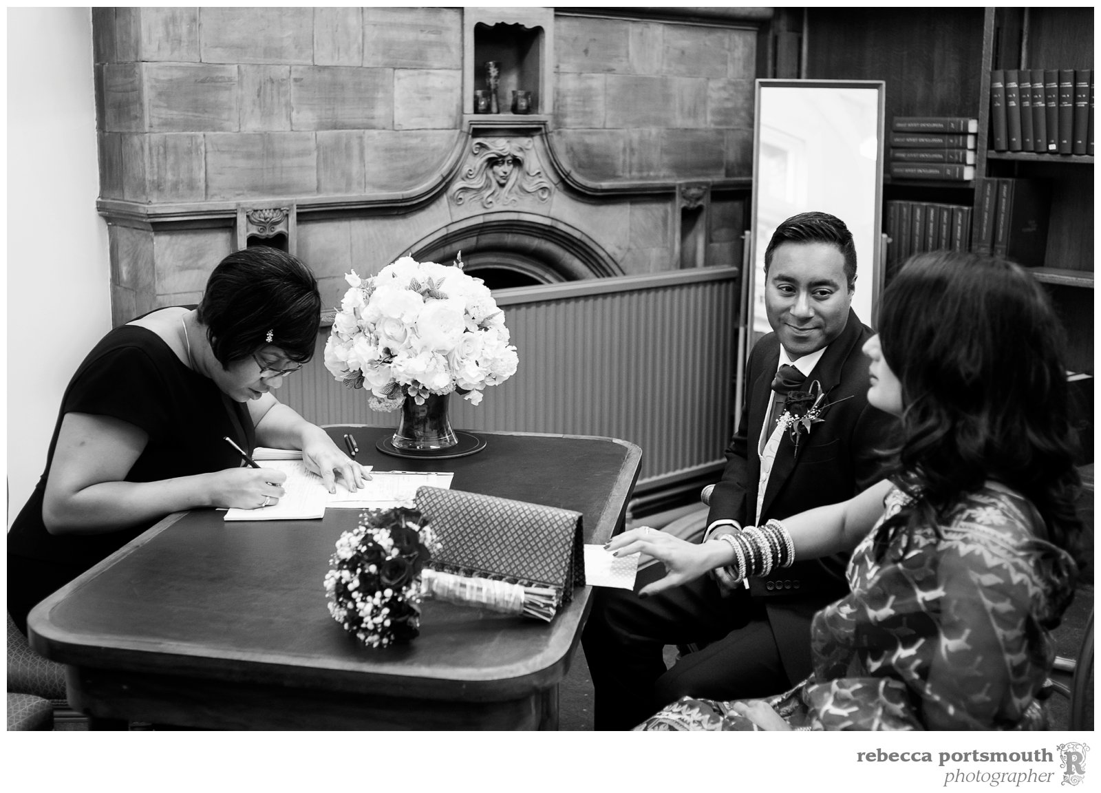 London bride and groom Tas and Ravi check civil wedding ceremony details with a Westminster registrar in the Elizabeth Barrett waiting room.