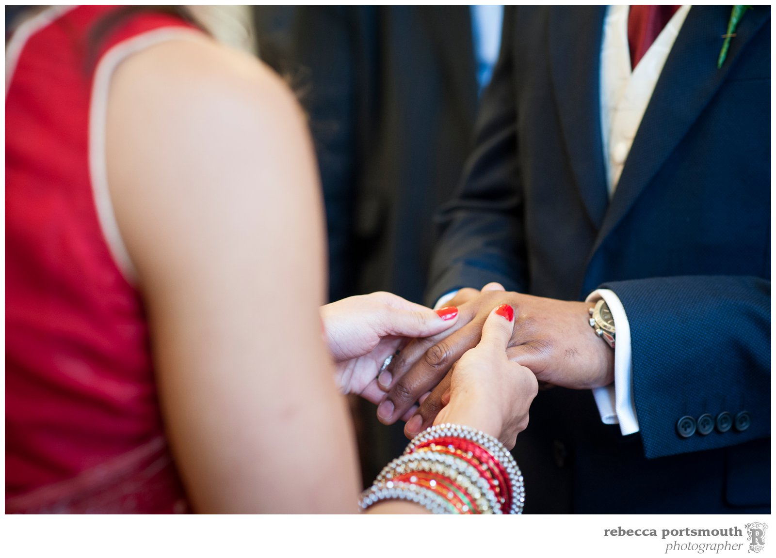 A close-up photograph of the bride and groom's hands during their Mayfair Library wedding ceremony in Westminster.