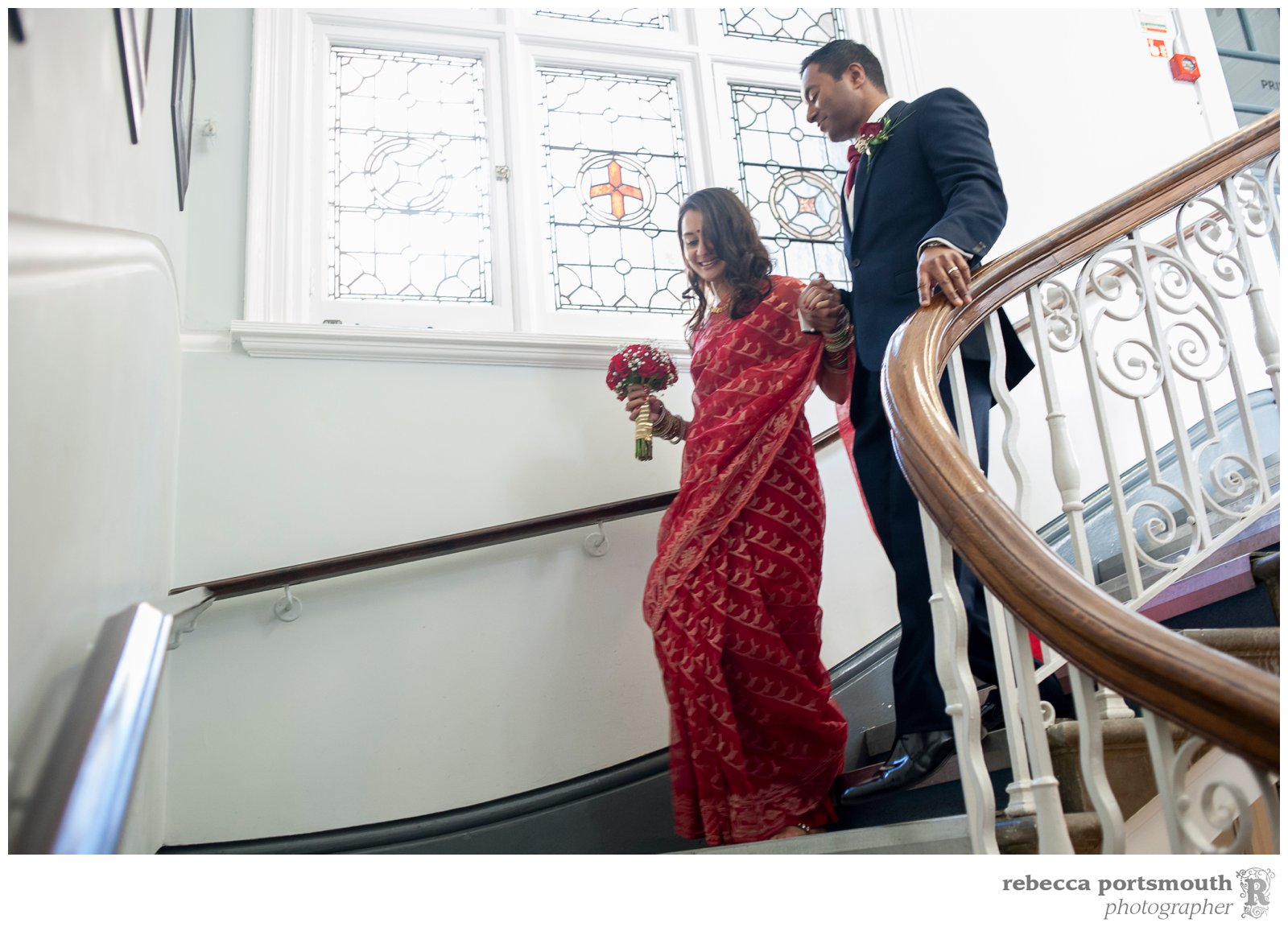 The bride and groom descend the period wooden stairs at Mayfair Library in South Audley Street, ready to be covered in confetti by their guests.