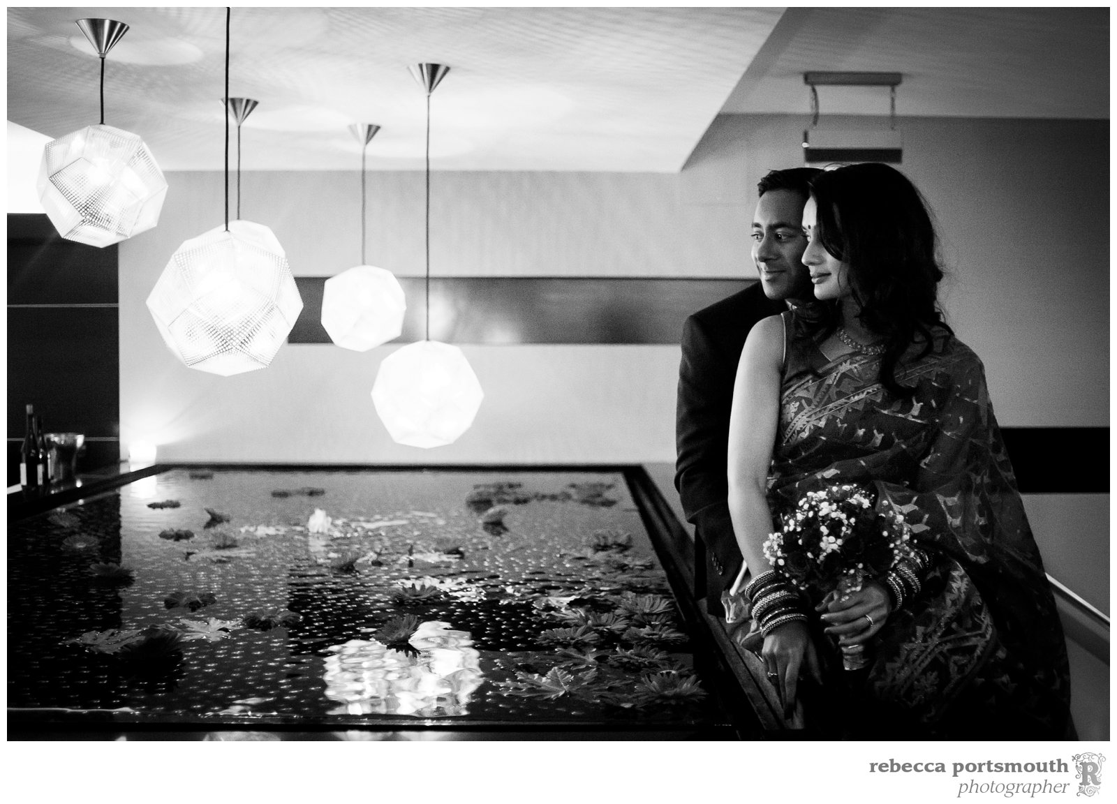 A bride and groom sit next to the water feature in Benares before their wedding breakfast.