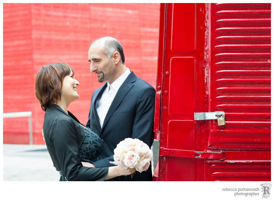 A bride and groom with a red van outside the National Theatre's red shed