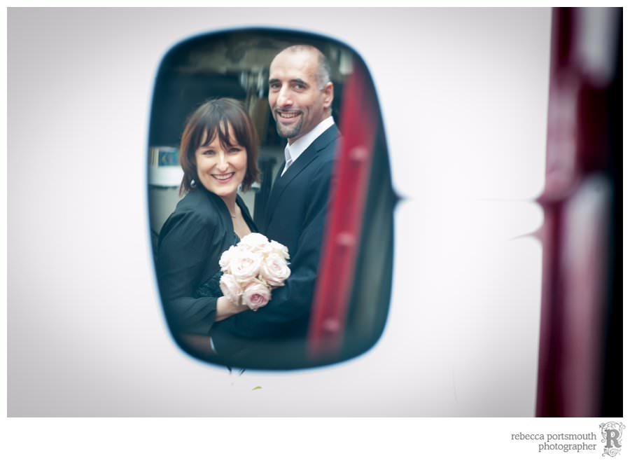 A bride and groom reflection in a wing mirror during their London South Bank wedding portraits