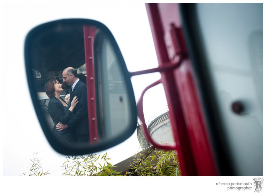A bride and groom in a candid wing mirror photograph of a red van on London's South Bank - in a wedding portrait shoot