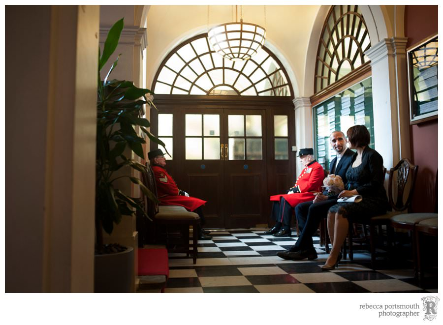 A bride and groom and two Chelsea Pensioners wait in the Royal Borough of Kensington and Chelsea Register Office Waiting Room