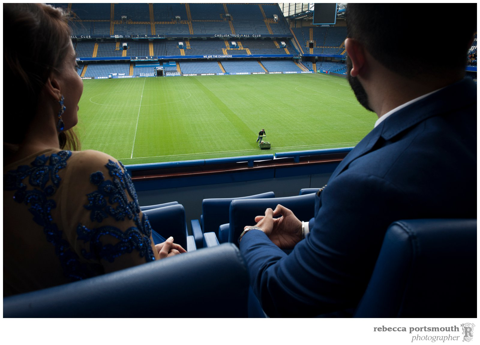 The bride and groom sit in the stands while groundsmen work on the Chelsea Football Club pitch, ready for a game in two days.