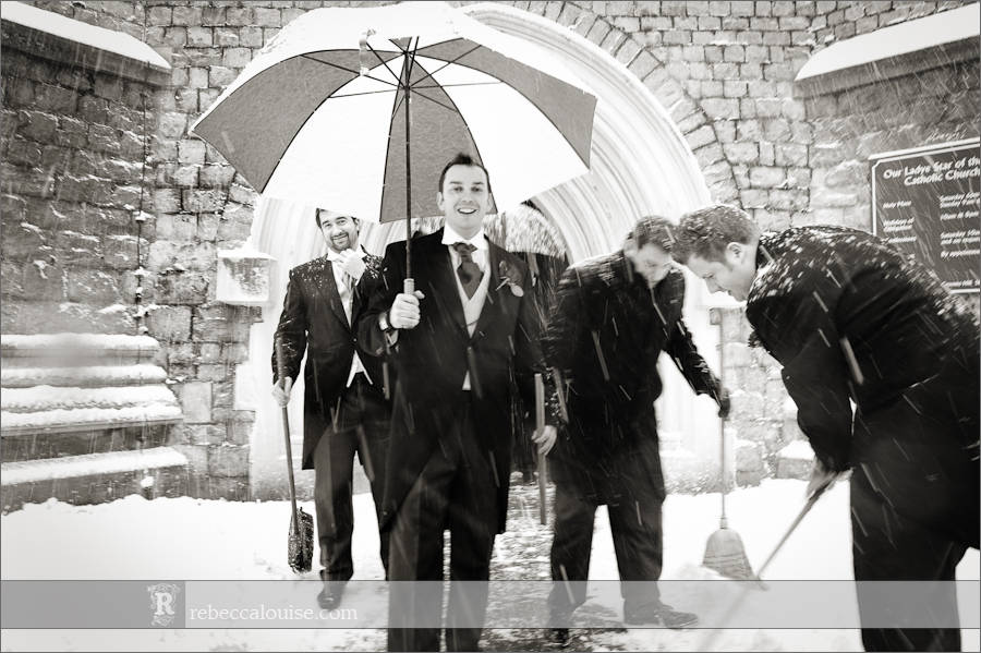 Star of the Sea Church wedding where the groom Charlie shelters under a golfing umbrella from the snow
