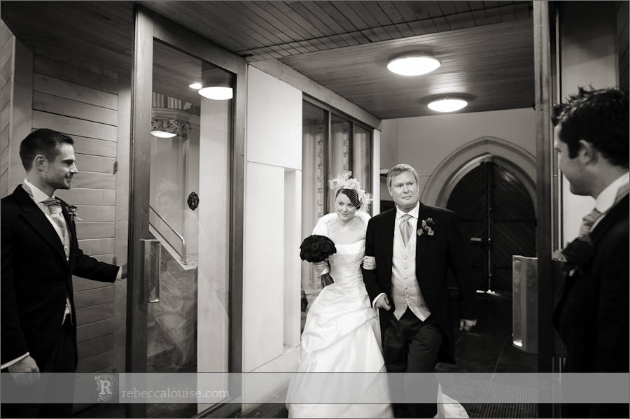 A bride and her father enter her Star of the Sea Church wedding, flanked by ushers