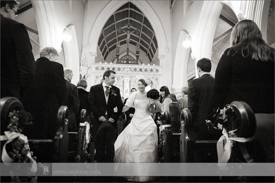 Star of the Sea Church wedding photographer Rebecca Portsmouth: a photo of Louise and Charlie leaving their winter wedding ceremony .