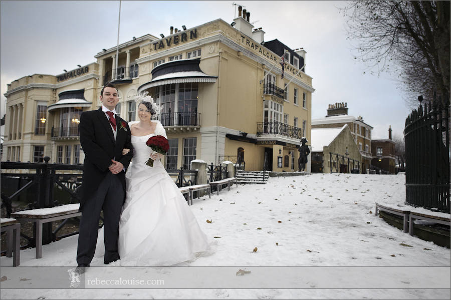 Bride and groom Louise + Charlie outside the Trafalgar Tavern in Greenwich on their snowy winter wedding day