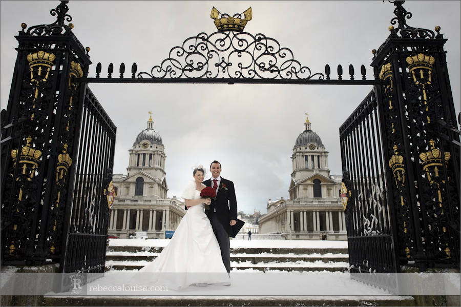 Bride and groom Louise + Charlie framed by the Old Royal Naval College (ORNC) Water Gate in the snow during their winter wedding portraits