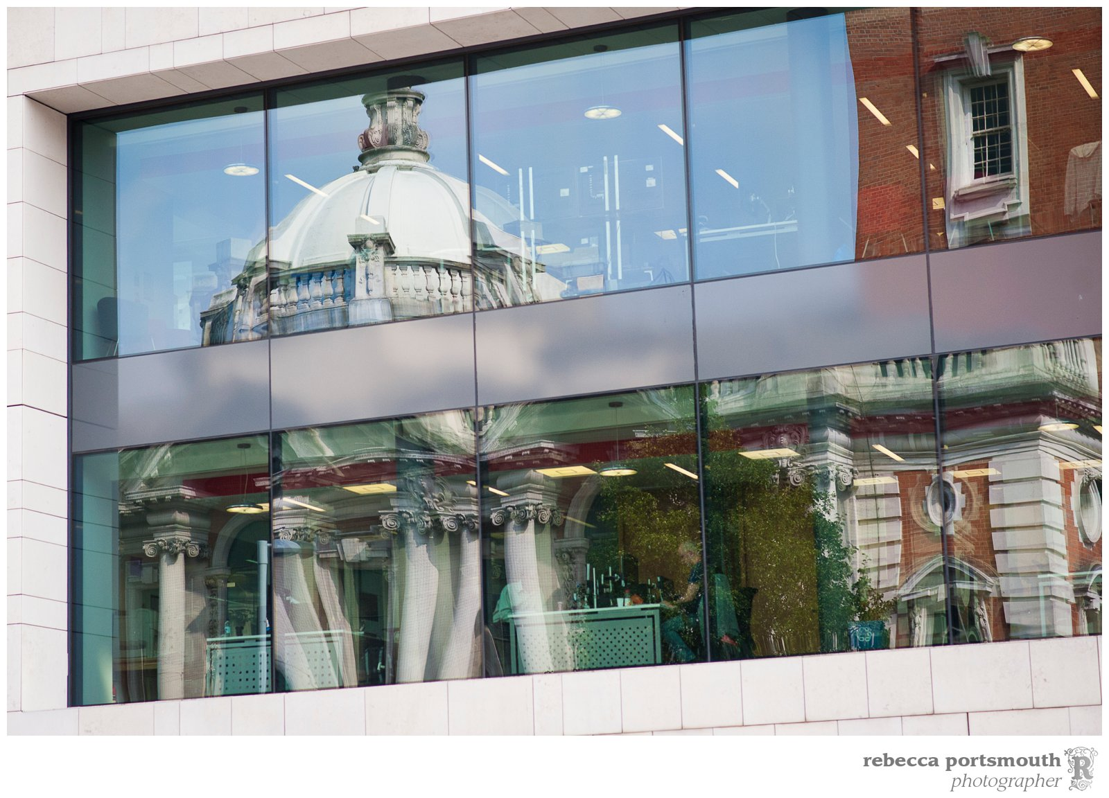 The Royal Borough of Greenwich Town Hall reflected in a modern glass building opposite