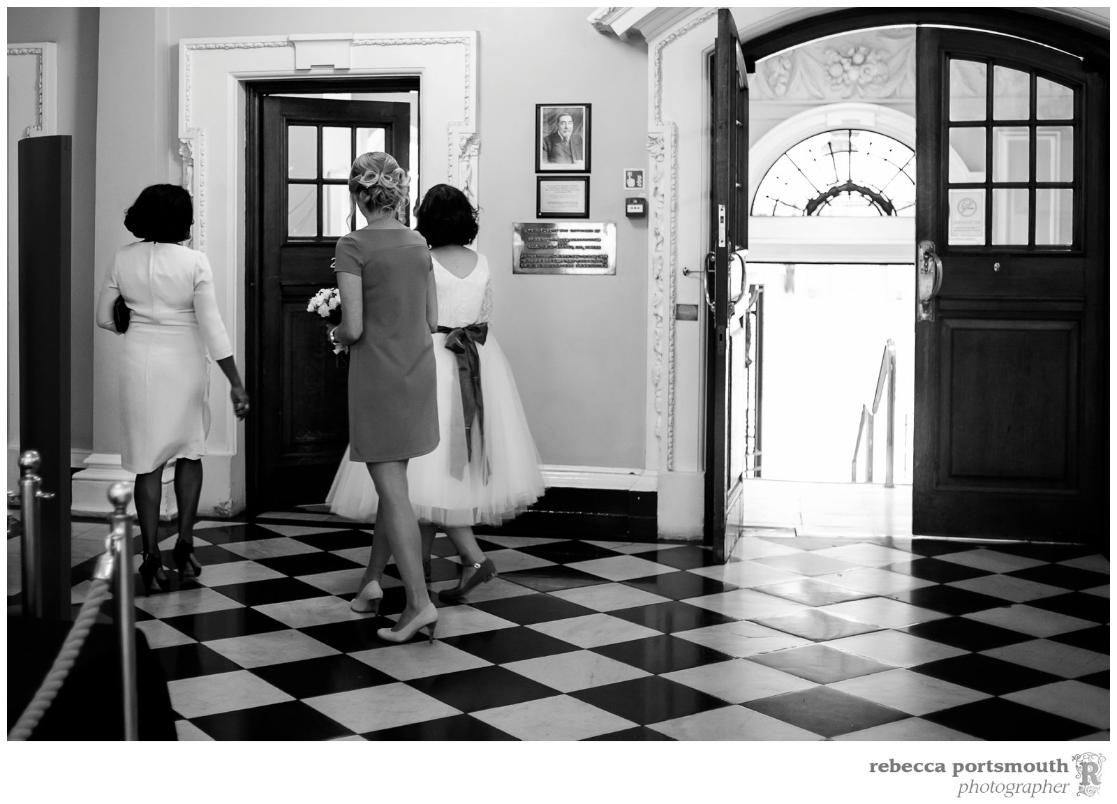 A bride and her bridesmaids enter Woolwich Town Hall, home of the Royal Borough of Greenwich, to hide from the groom before the civil wedding ceremony, photographed by Greenwich Registry Office wedding photographer Rebecca Portsmouth.