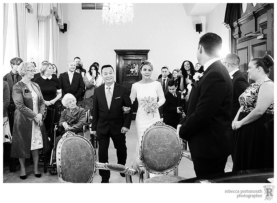 Bride Katie meets her groom James at the front of the Brydon Room, at the start of their Chelsea civil wedding ceremony.