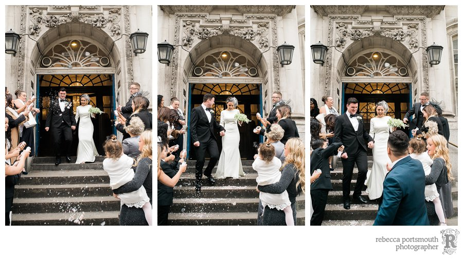 Stylish bride and groom on the famous steps of Chelsea Old Town Hall on the Kings Road with their guests and confetti.